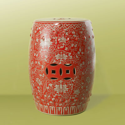 a red ceramic garden stool with Buddhist orchid design