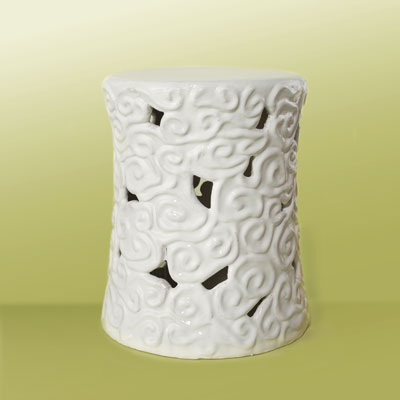 a white ceramic garden stool with raised, swirly cloud designs