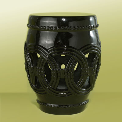 a black, fluted fiberglass garden stool