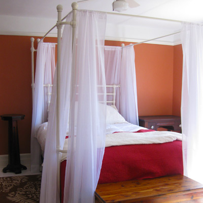 farmhouse bedroom with orange walls and canopy bed