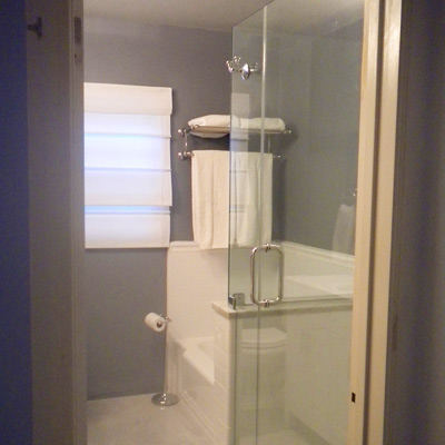 bath with gray walls, glass shower