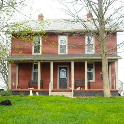 farmhouse with red siding and pavers front porch