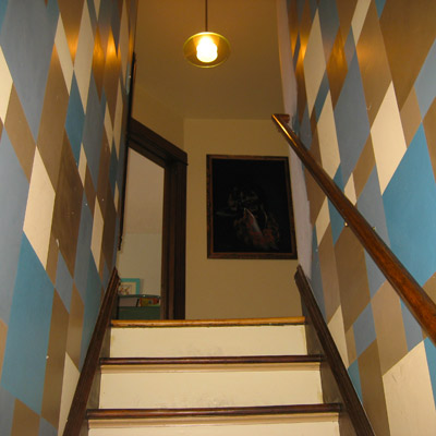 stairway walls painted with blue, brown and off-white geometric pattern