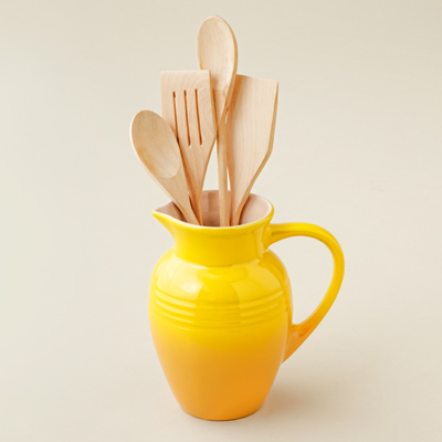 stoneware pitcher with yellow enamel finish and wooden utensils