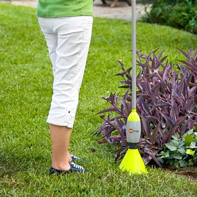 woman uses a hand weeder on her lawn