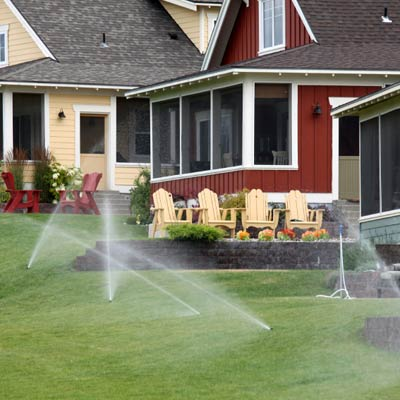 water sprinklers irrigating a landscaped residential area