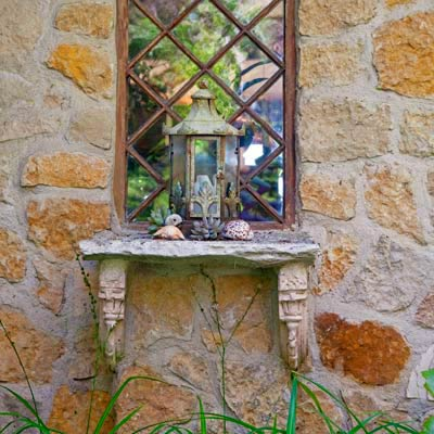 decorative lantern on a stone shelf in a garden 