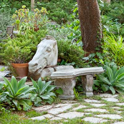garden bench with concrete horse's head 