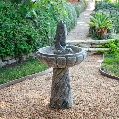 birdbath with fish statue at center in garden path