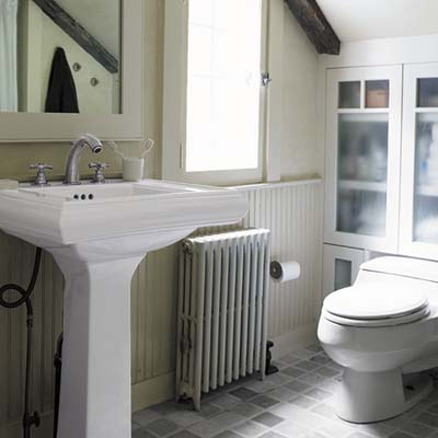 master bathroom has a pedestal sink, custom cabinets, marble floor tiles and radiant heating