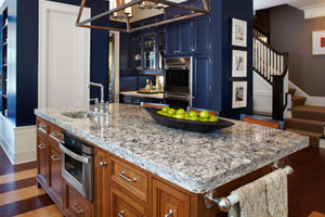 black and gray quartz kitchen countertop on island with blue kitchen cabinets in background