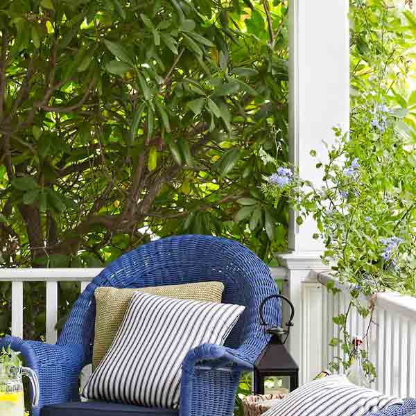 upgrade outdoor room, white porch with bright blue painted wicker furniture and line of trees as greenery wall for privacy
