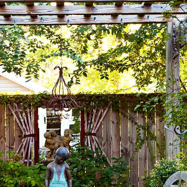 upgrade outdoor room, pergola with stone floor, antique looking mirror hanging on privacy wall