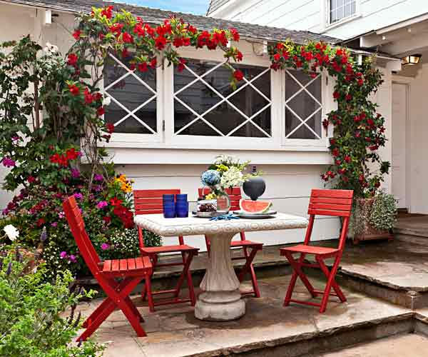 upgrade outdoor room, patio with concrete table and red painted chairs, vine creeping along adjacent window