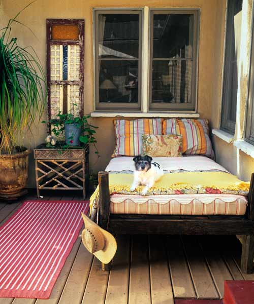 upgrade outdoor room, deck with cedar frame bed, dog, rug and bedside table with potted plants