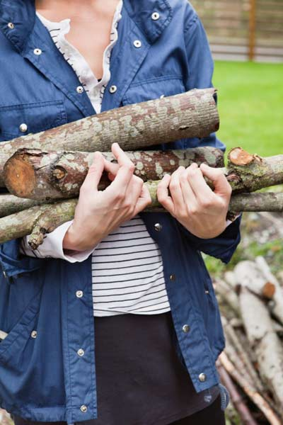 woman carrying firewood, homeowner survival skills