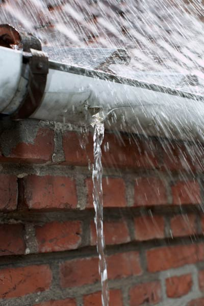 gutter with rain pouring through hole, homeowner survival skills