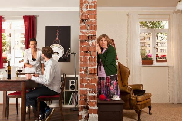 woman listening to noisy neighbors, homeowner survival skills