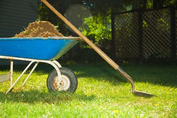 wheelbarrow full of dirt and a shovel on a lawn, homeowner survival skills
