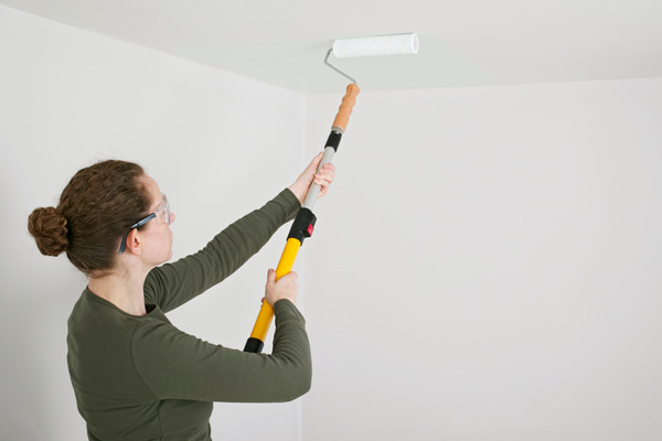 woman painting ceiling with roller, homeowner survival skills