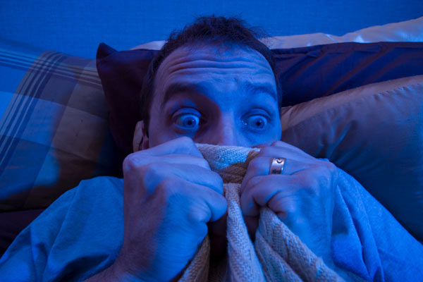 man scared and hiding under his bed sheets, homeowner haunted house noises