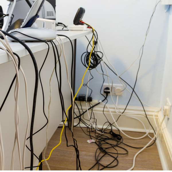 10 uses for weatherstripping tangled wires behind desk of electronics