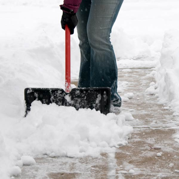 person shoveling snow on walkway or driveway