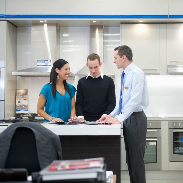 young couple talking to appliance salesman