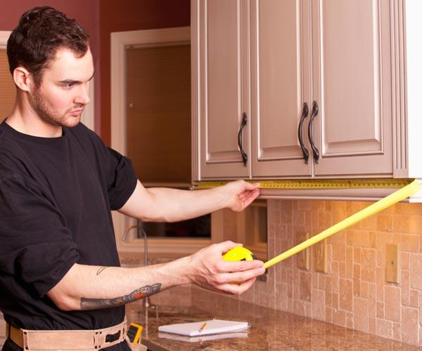 man measuring kitchen cabinet