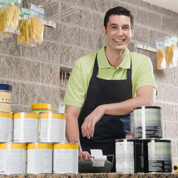 man behind counter at hardware store with paint supplies