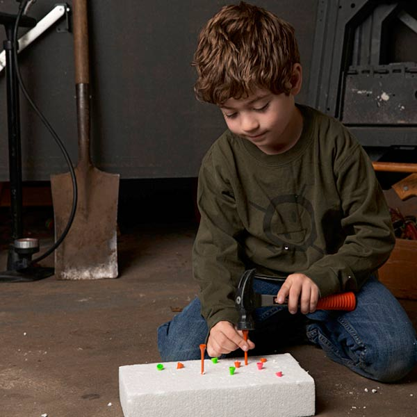 little boy practicing hammering golf tees into piece of foam