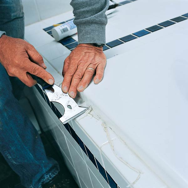 scraping caulk from around perimeter of old bath tub with painting 5 in 1 tool