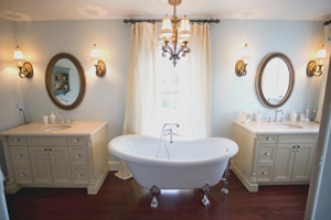 bath with chandelier lighting, two vanities and a standalone tub