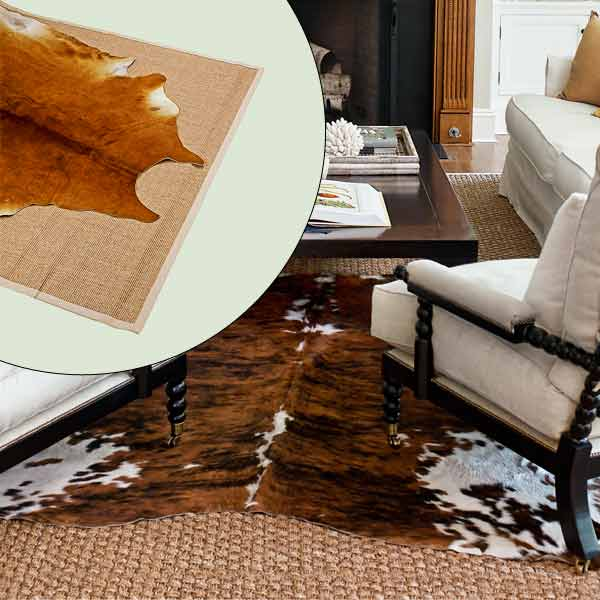 get this look naturalist living room with cow hide rug layered over woven sisal rug
