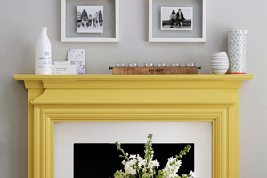 yellow painted mantel in gray and white living area