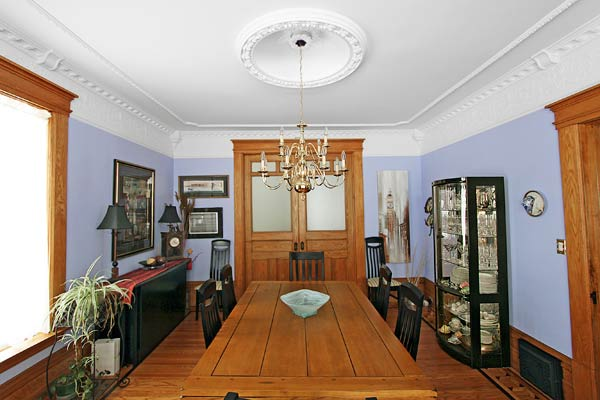 purple dining room with period details of ceiling dome, chandelier and detailed crown molding trim