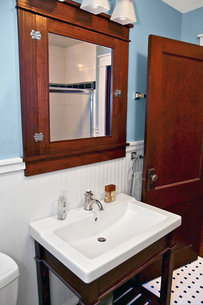bathroom after remodel with wood medicine cabinet and vanity