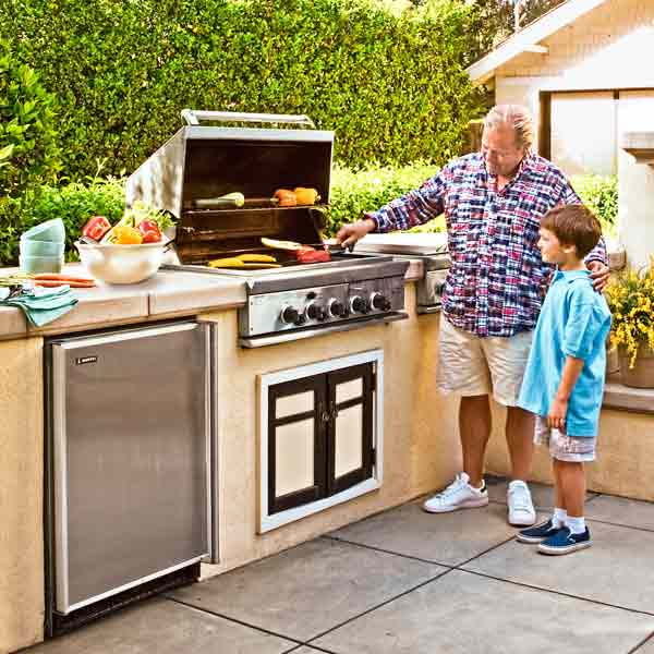 man and grandson looking at outdoor grill for backyard party
