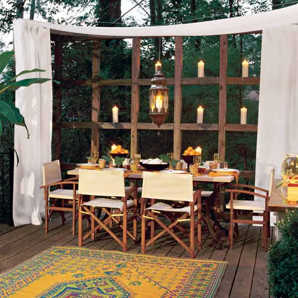 deck with curtain and outdoor seating area for backyard party