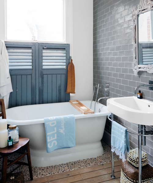 detail of accent wall made of neutral gray subway tile, easy budget bath upgrades
