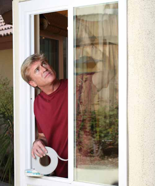 man checking weatherstripping on his windows, june fast fixes for upkeep