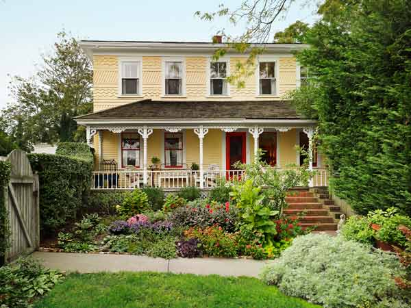 yellow exterior with victorian style trim after remodel of federal style house