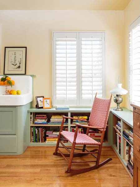 rocking chair in area with shelves full of recipe books, retro style kitchen with soft green cabinets and salvage apron sink