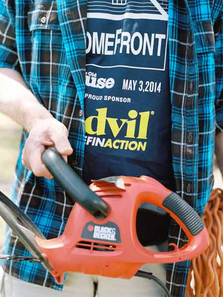 person wearing an advil shirt and holding a chainsaw, advil homefront webvertorial