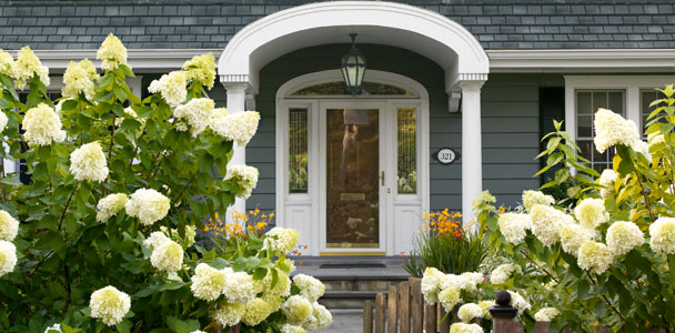 front door arch shielded by flowers, shrubs, and a picket fence for Before and After Front Yard: Private and Inviting