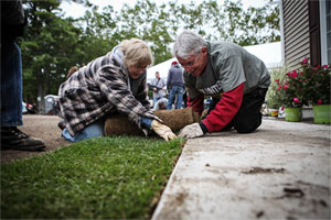 two volunteers roll out sod next to the walkway outside the veteran's special house project house