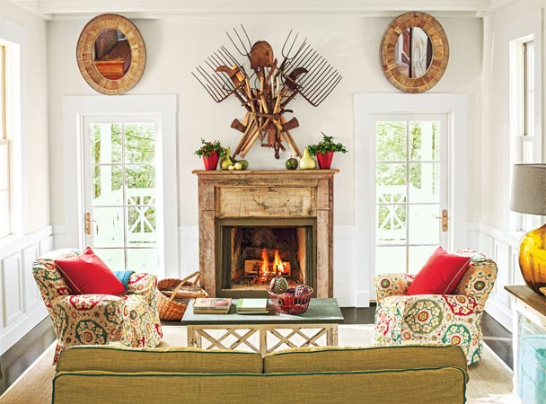 rustic-looking living space with pine-rimmed mirrors, a distressed wood mantle, two red planters, a roaring fire, a wall sculpture farming tools, patterned chairs, a zinc-top coffee-table, neutral couch and sisal rug