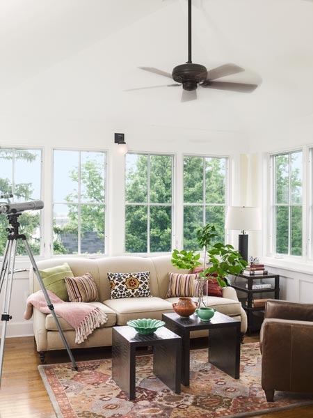 telescope pointed at the wrap-around windows behind a salmon-colored couch with end tables and tree-tops visible out the third-floor windows after this american foursquare house remodel