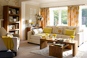 sunny neutrals on the walls and floor with citrusy accessories, warm wood furnishings, and an abundance of floral arrangements for this spring fresh living room