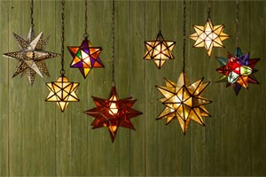 a row of eight multipointed, polyhedra pendant lights, some in a single color, some in multiple colors like stained glass, hanging against a weathered-look, green, wood-slat wall